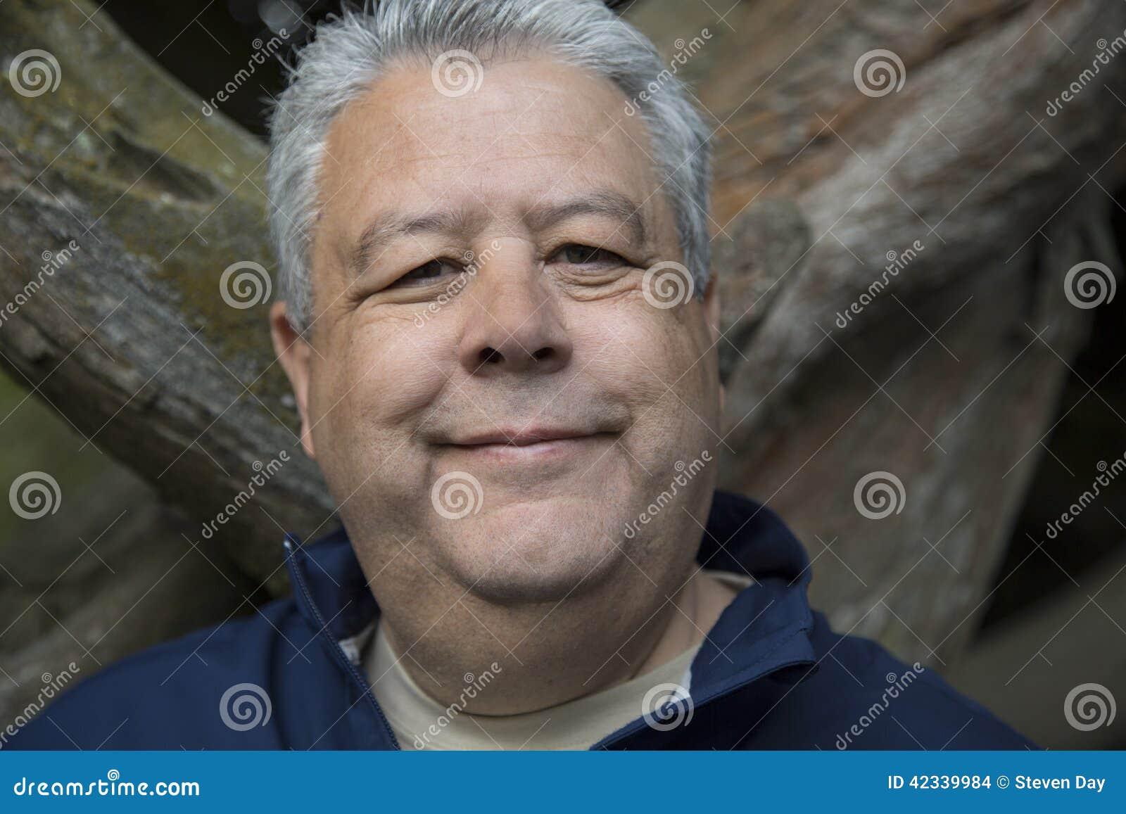 O meio envelheceu o homem que sorri no retrato exterior dentro para