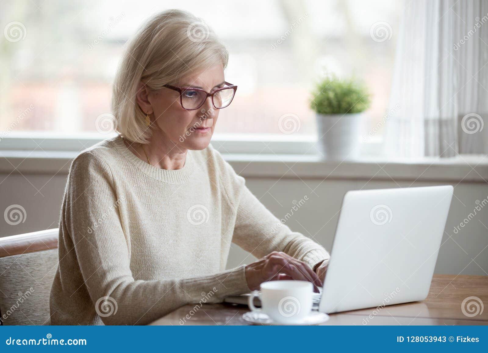 O meio maduro sério envelheceu a mulher de negócio que usa o portátil que datilografa o em