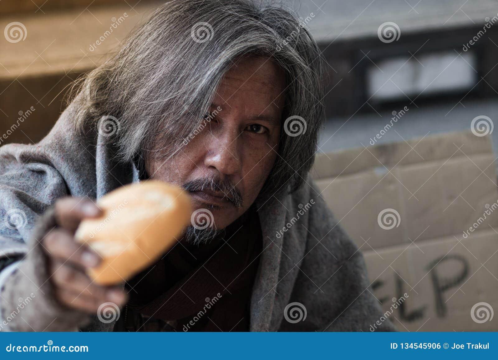 O mendigo masculino, dando o pão ou o alimento para fazer o homem desabrigado com fome têm a cara feliz