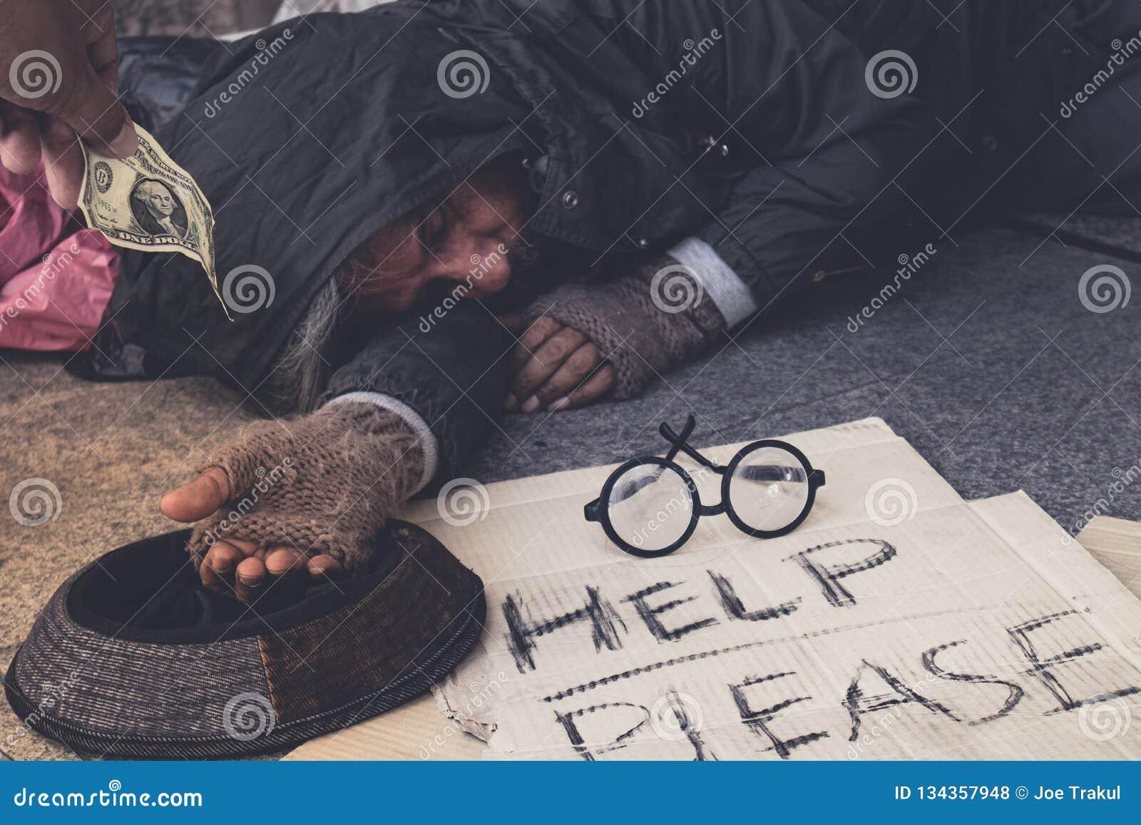 O mendigo masculino, homem com fome desabrigado para mostrá-lo para entregar quer o dinheiro do alimento na rua na cidade, pessoa