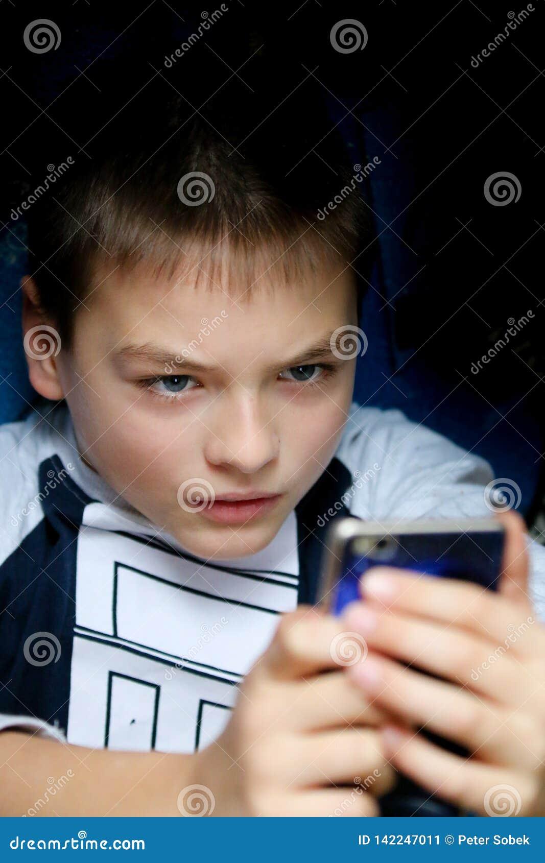 O menino é referido sobre seu telefone celular
