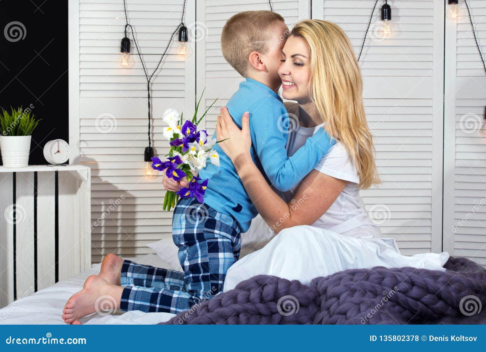 O menino acorda a mamã e dá-lhe um ramalhete das flores na cama Comemorando o dia da mulher Dia do `s da matriz