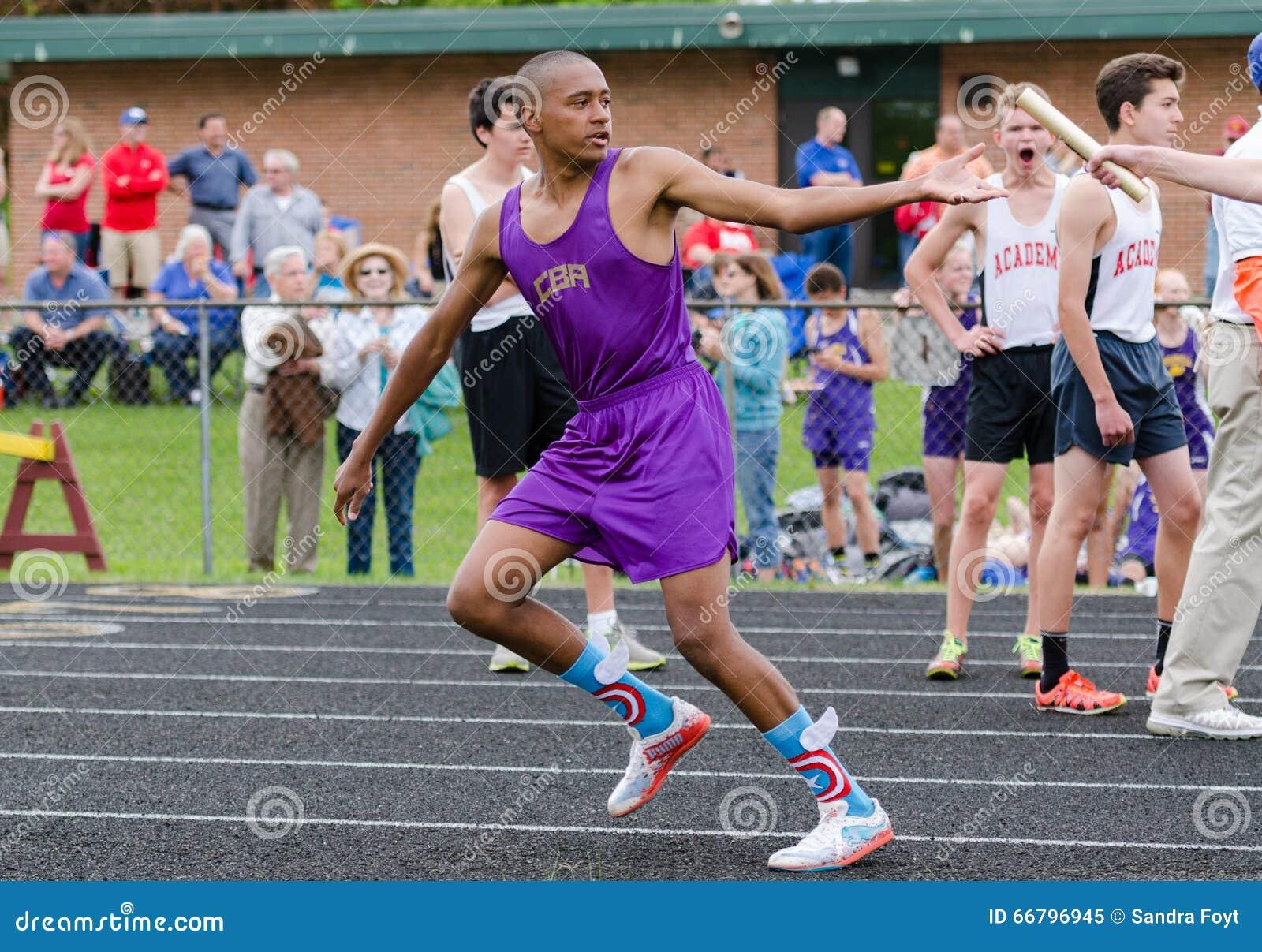 O menino adolescente aceita o bastão na reunião exterior do atletismo