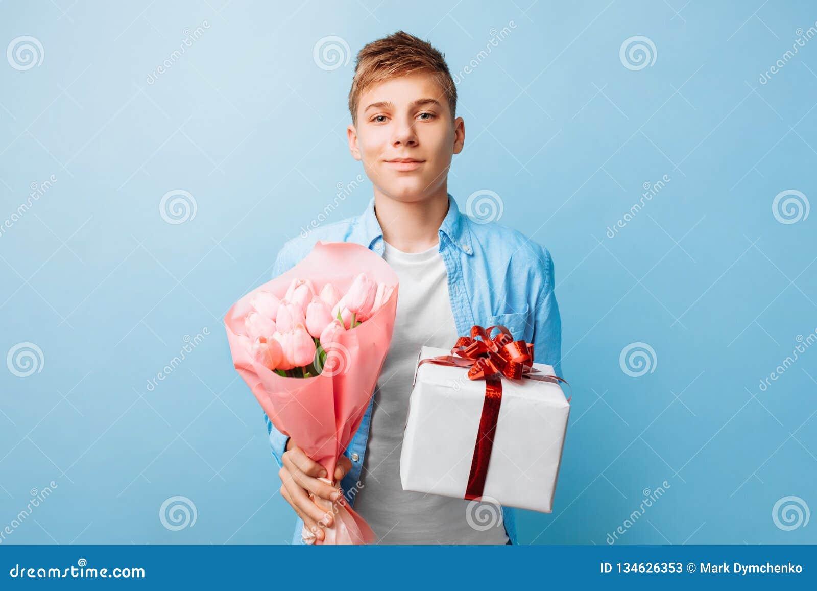 O menino adolescente dá um presente e as flores, um homem no amor, em um fundo azul