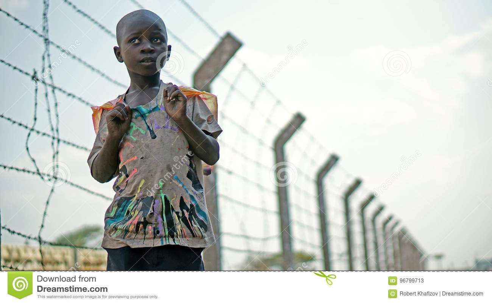 O menino africano está em um fundo do arame farpado ao longo da estrada de ferro
