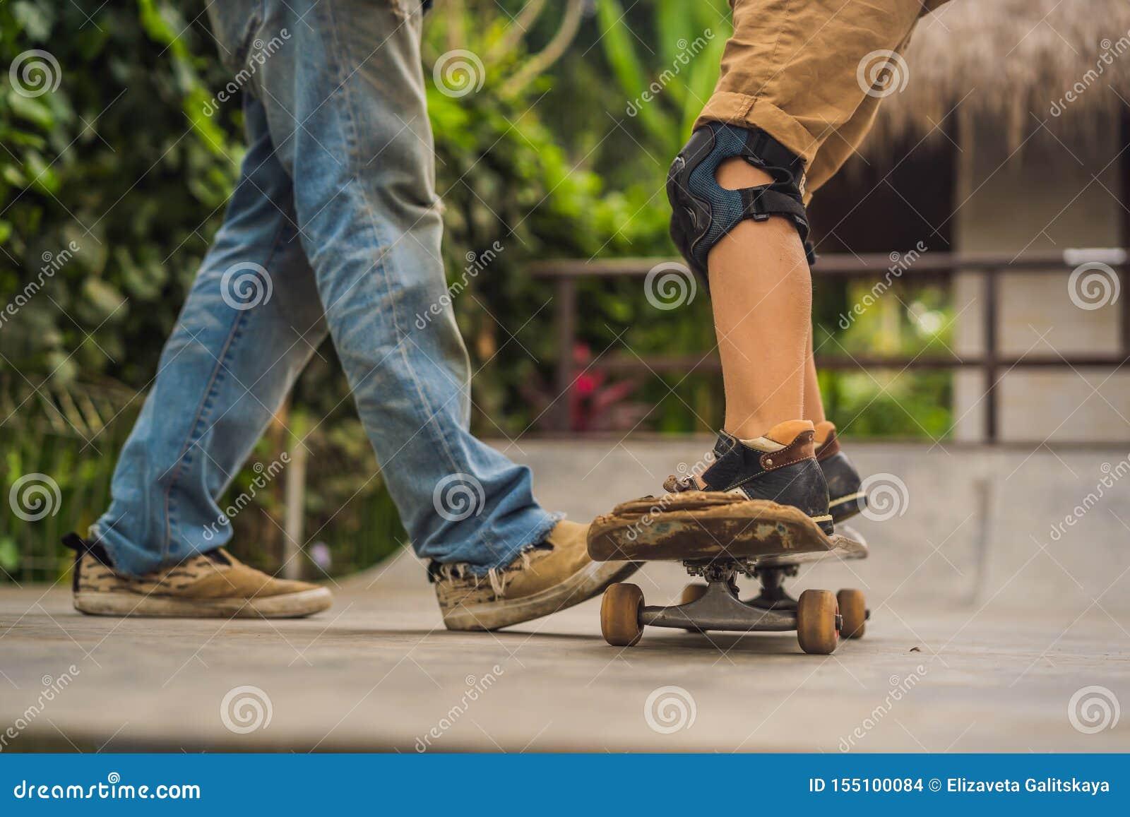 O menino atlético aprende ao skate com um instrutor em um parque do patim Educação das crianças, esportes
