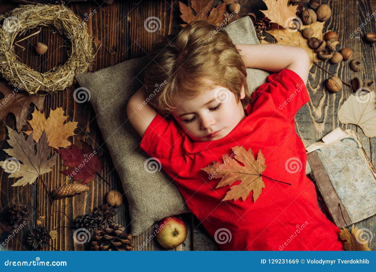 O menino bonito da criança pequena está preparando-se para o outono A criança anuncia seus produtos e serviço Descanso louro do r