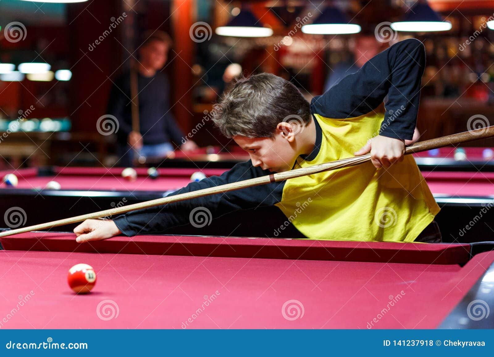 O menino bonito na camisa amarela de t joga o bilhar ou a associação no clube A criança aprende jogar a sinuca Menino com sugestã