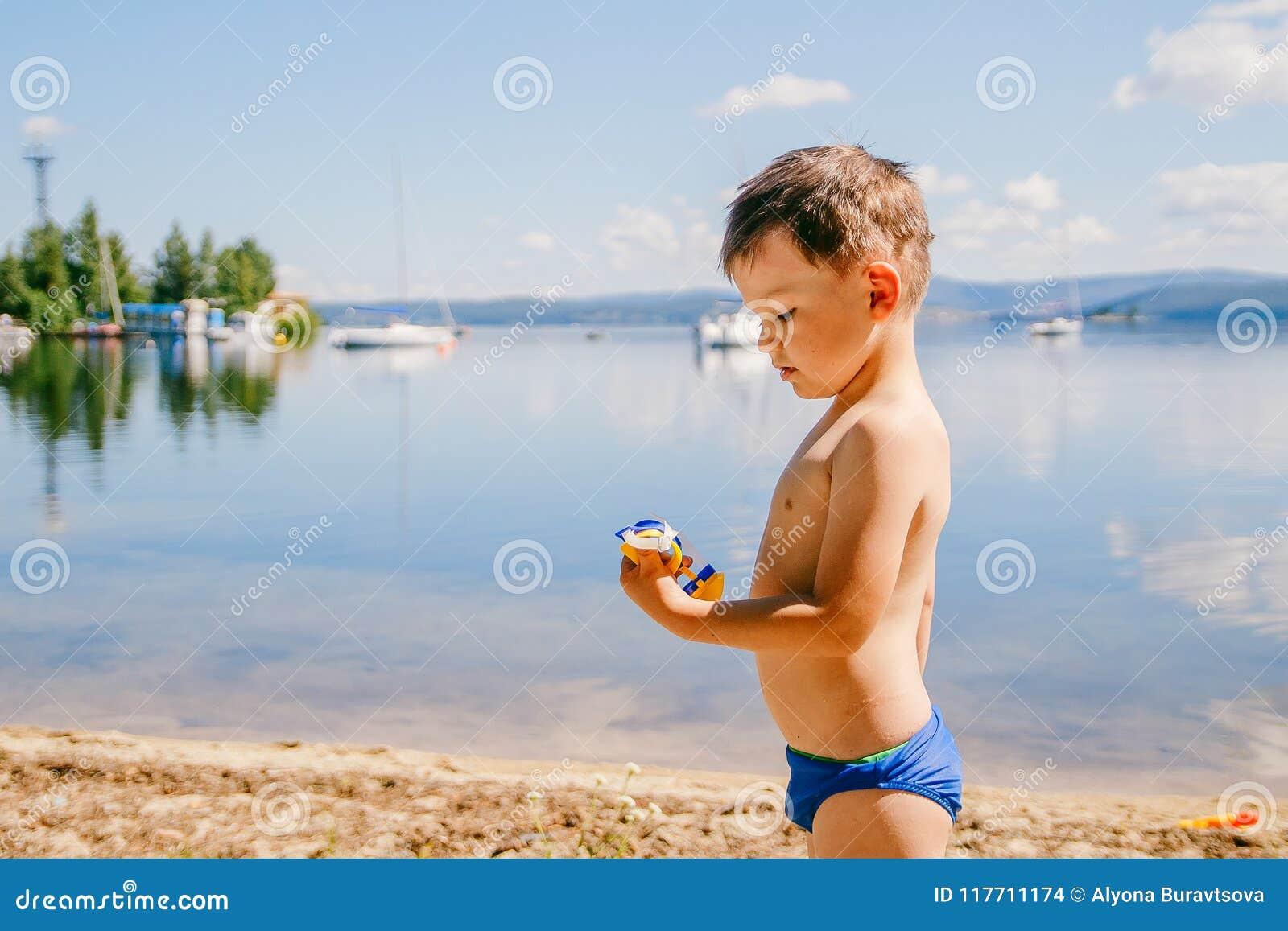 O menino bronzeado de três anos em troncos de natação joga no lago no verão, férias de verão, infância