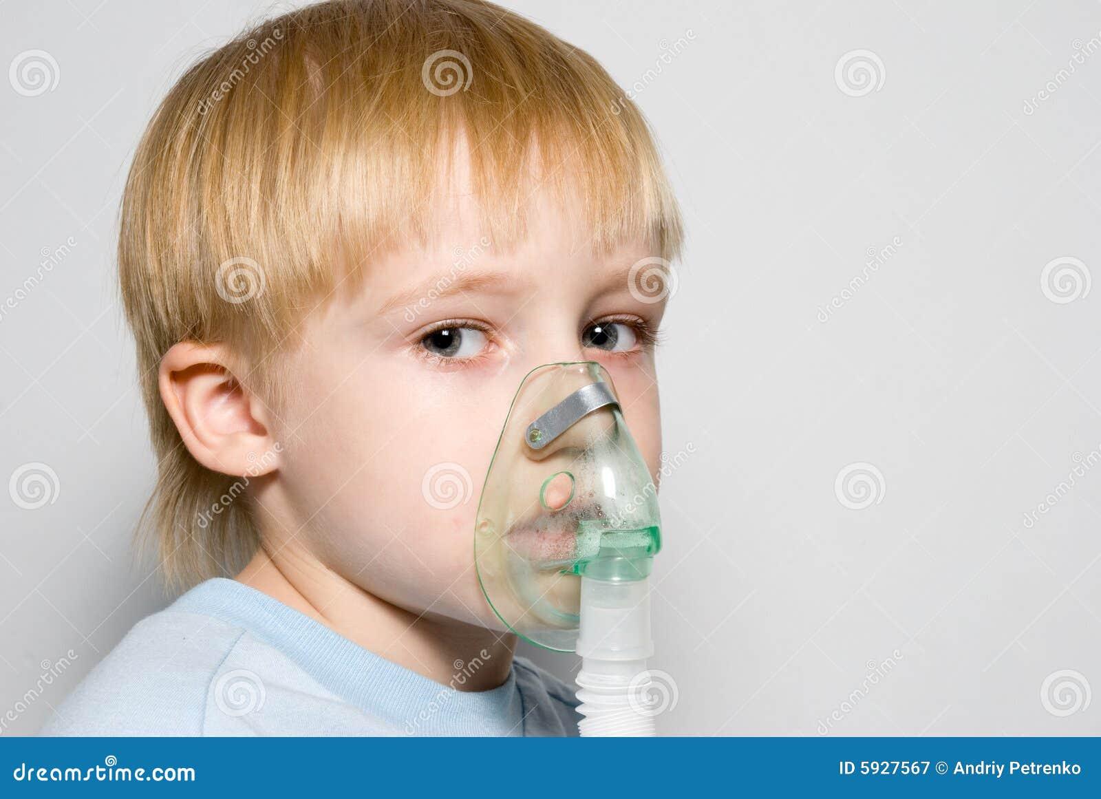 O menino com uma máscara na face