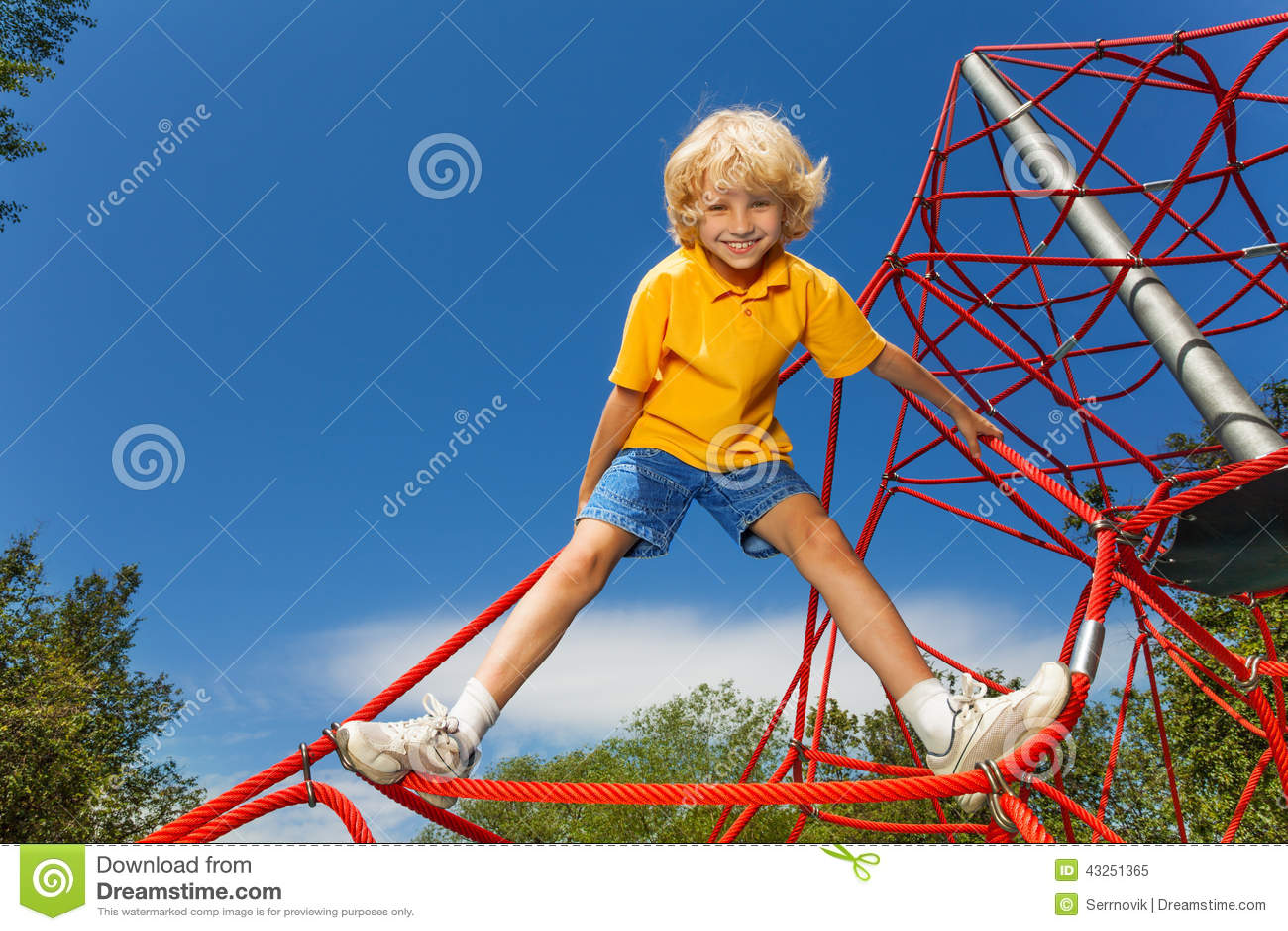 O menino de sorriso está na corda vermelha com pés distante