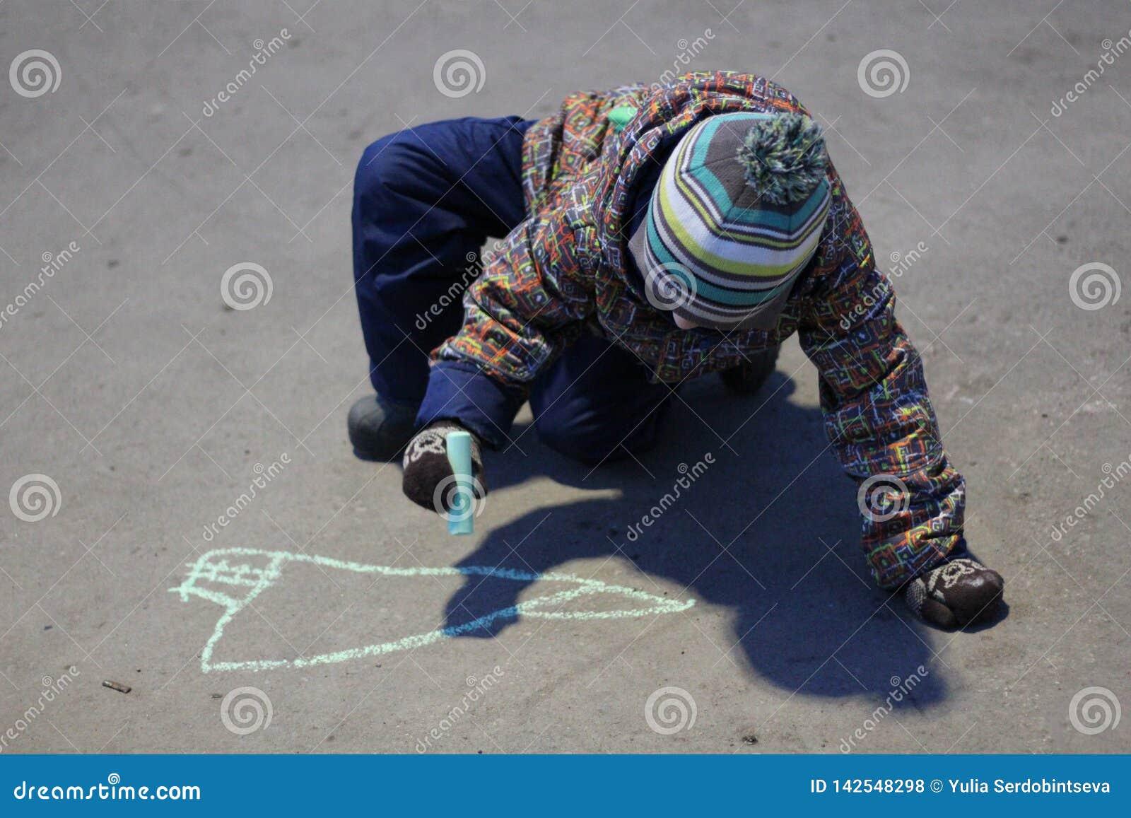 O menino de três anos na roupa de rua e em um chapéu tira com giz no pavimento na mola adiantada