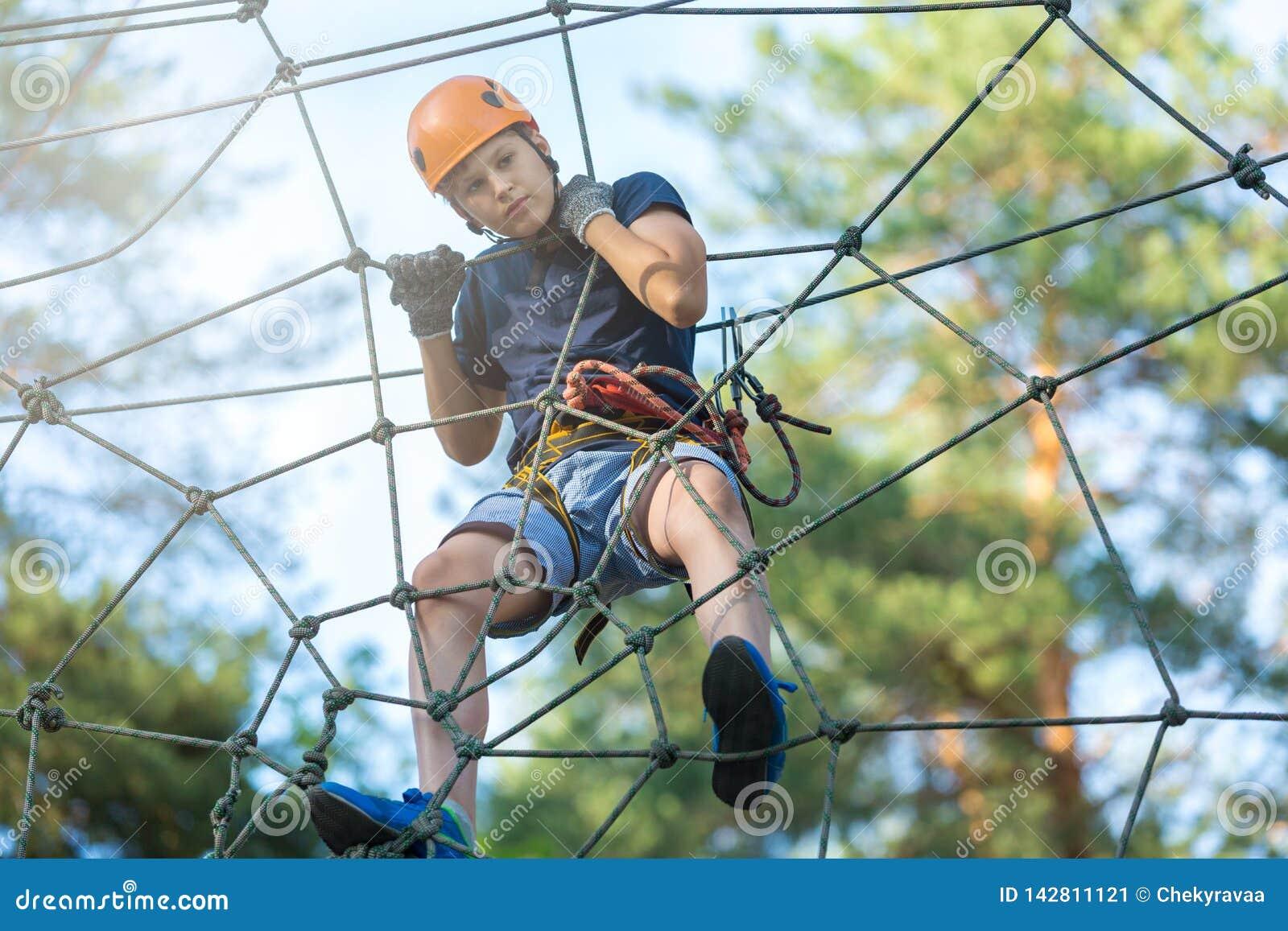 O menino desportivo, novo, bonito na camisa branca de t passa seu tempo no parque da corda da aventura no capacete e no equipamen