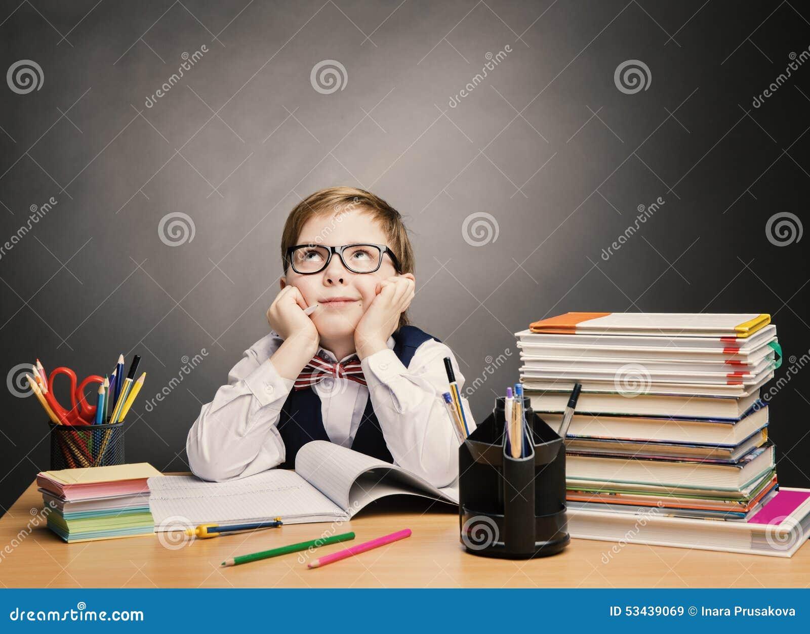 O menino do aluno nos vidros pensa a sala de aula, livro dos estudantes da criança