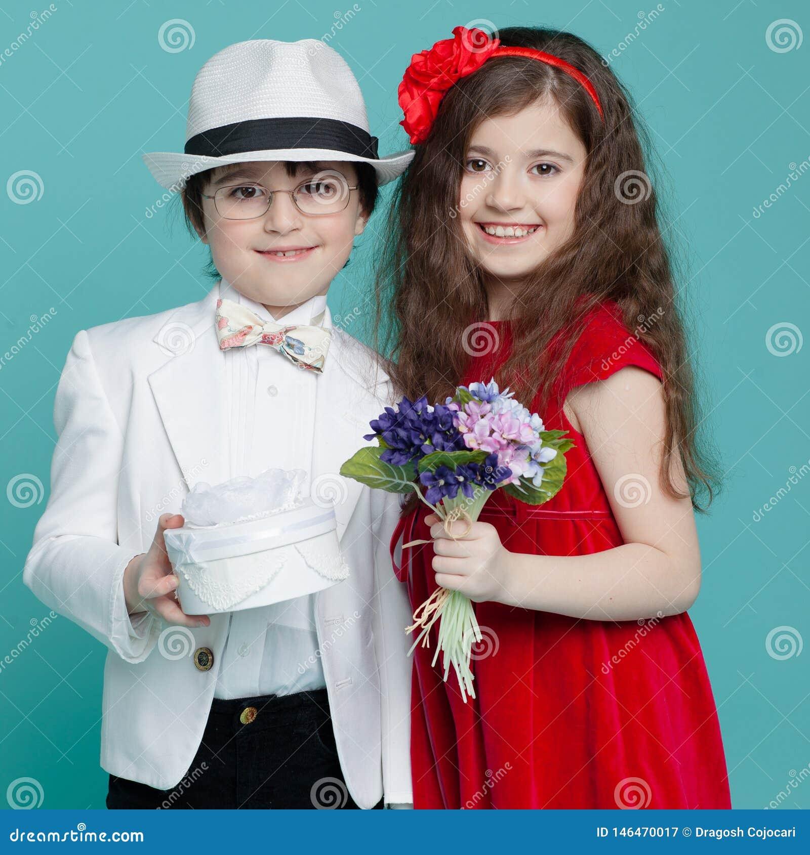 O menino e a menina adoráveis, vestem o terno elegante e o vestido vermelho, levantando no estúdio, isolado no fundo de turquesa