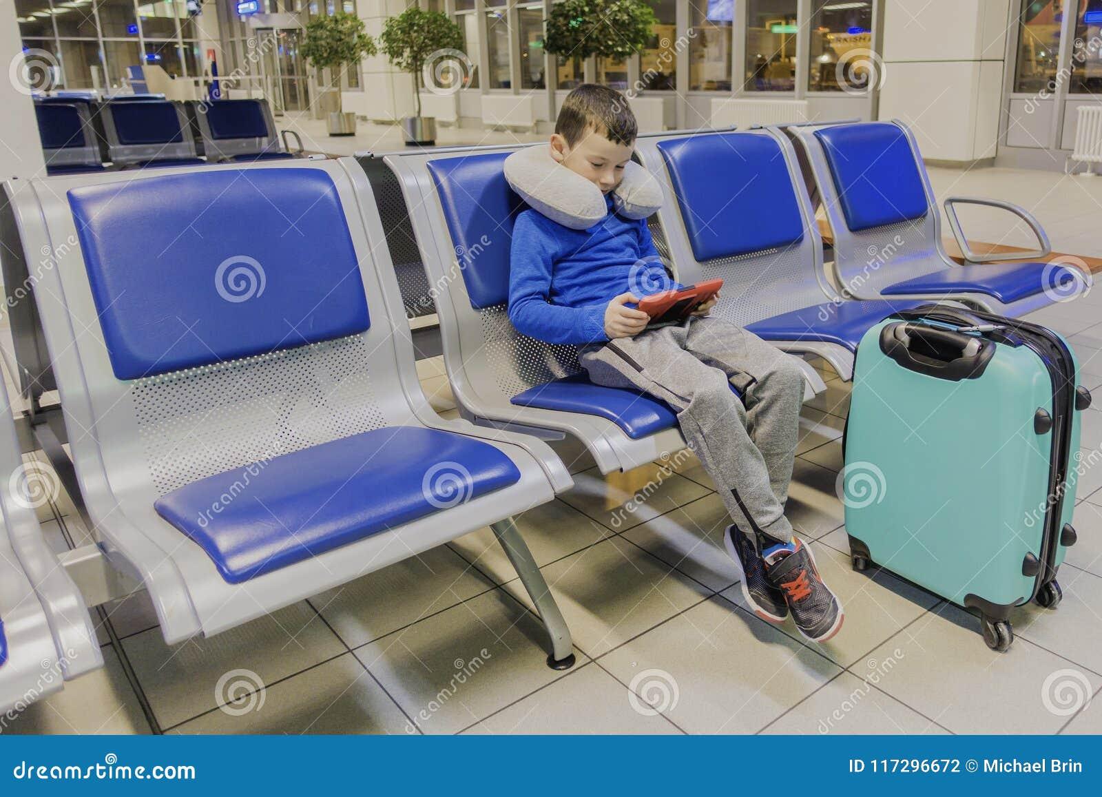 O menino em um aeroporto vazio um espera o plano e os jogos em seu dispositivo favorito