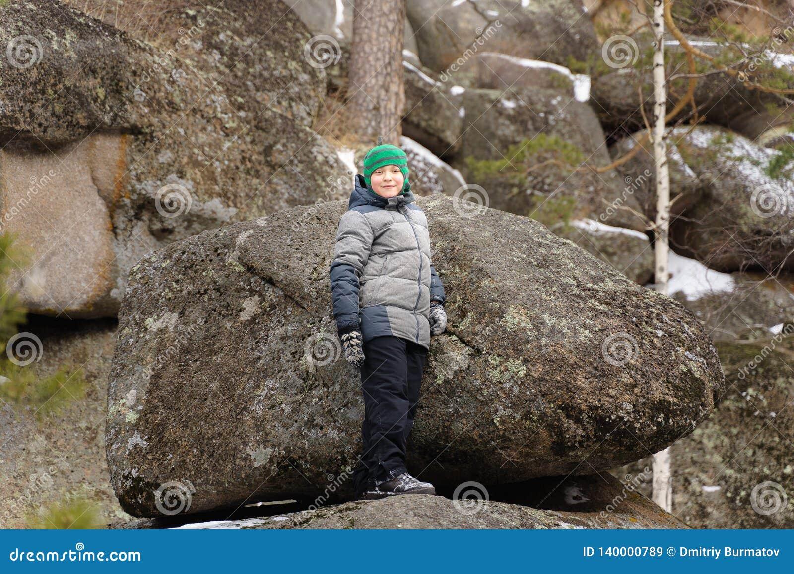 O menino escalou em um pedregulho no meio das rochas