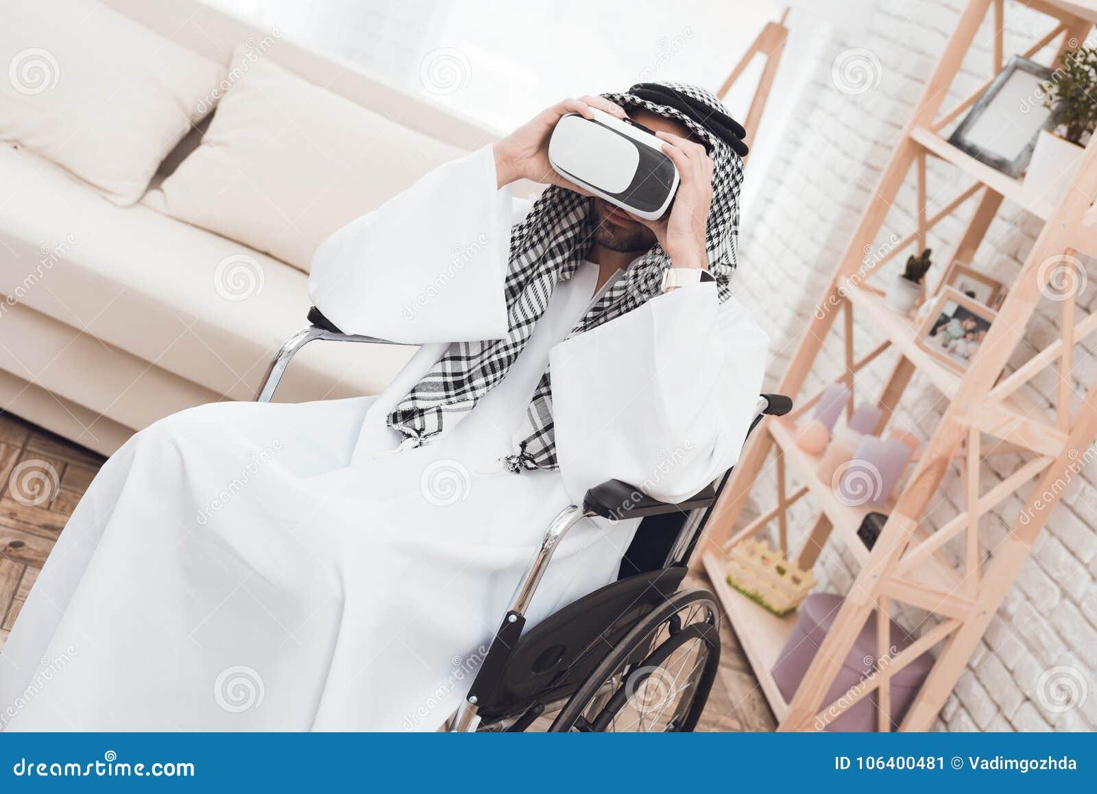 O menino está atrás de um homem árabe em uma cadeira de rodas que olhe em vidros da realidade virtual