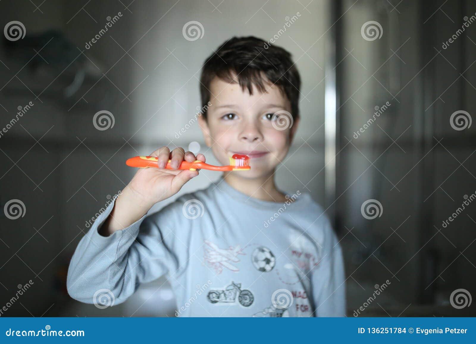 O menino está escovando seus dentes