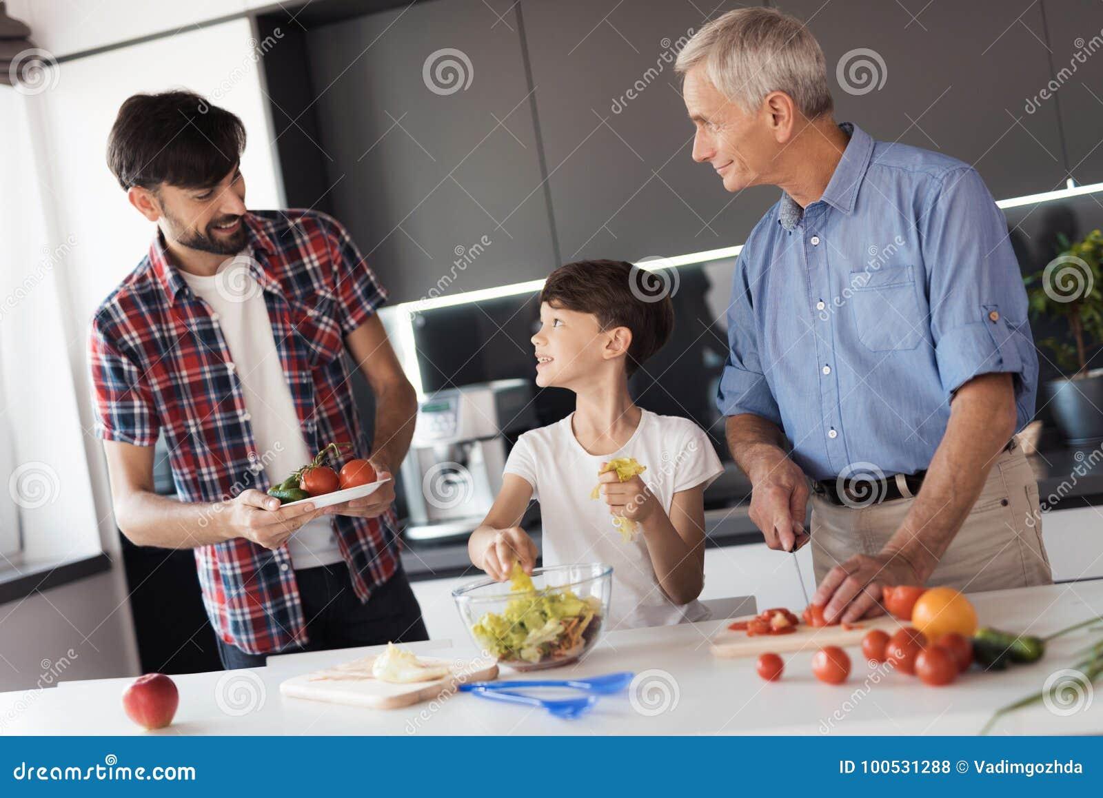 O menino está preparando uma salada para o jantar no dia da ação de graças com seus pai e avô