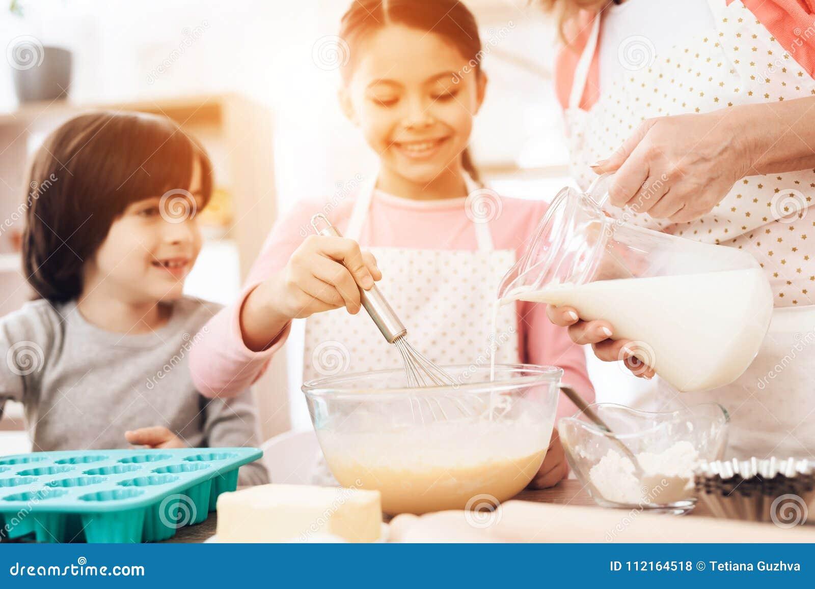 O menino feliz olha a menina que está batendo ovos na bacia, onde a avó bonita derrama o leite do jarro