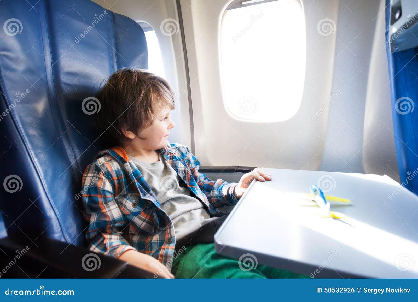 O menino feliz senta-se no plano com modelo do brinquedo na tabela