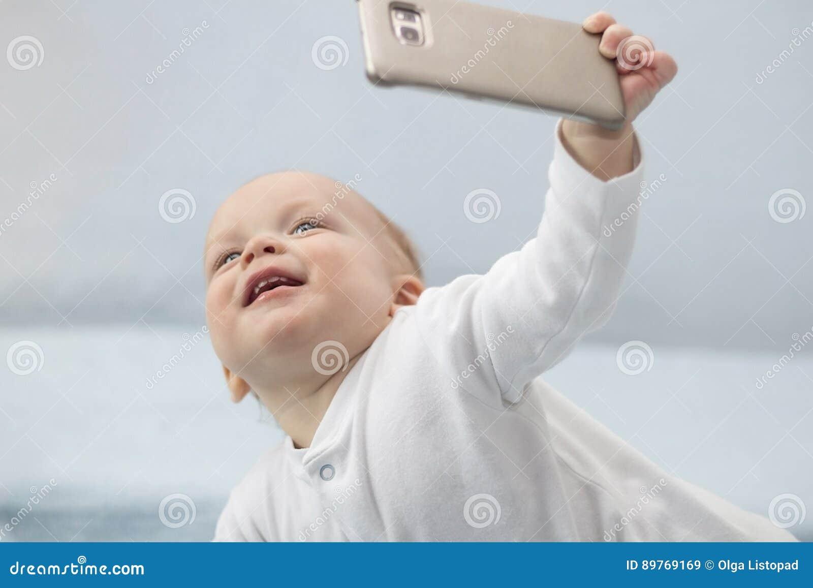 O menino infantil bonito faz o selfie com um telefone celular Criança de sorriso adorável da criança que toma uma foto do selfie