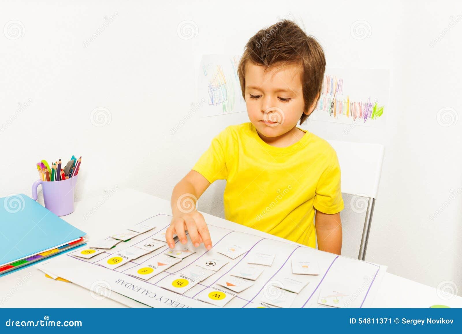 O menino joga no jogo tornando-se que aponta no calendário