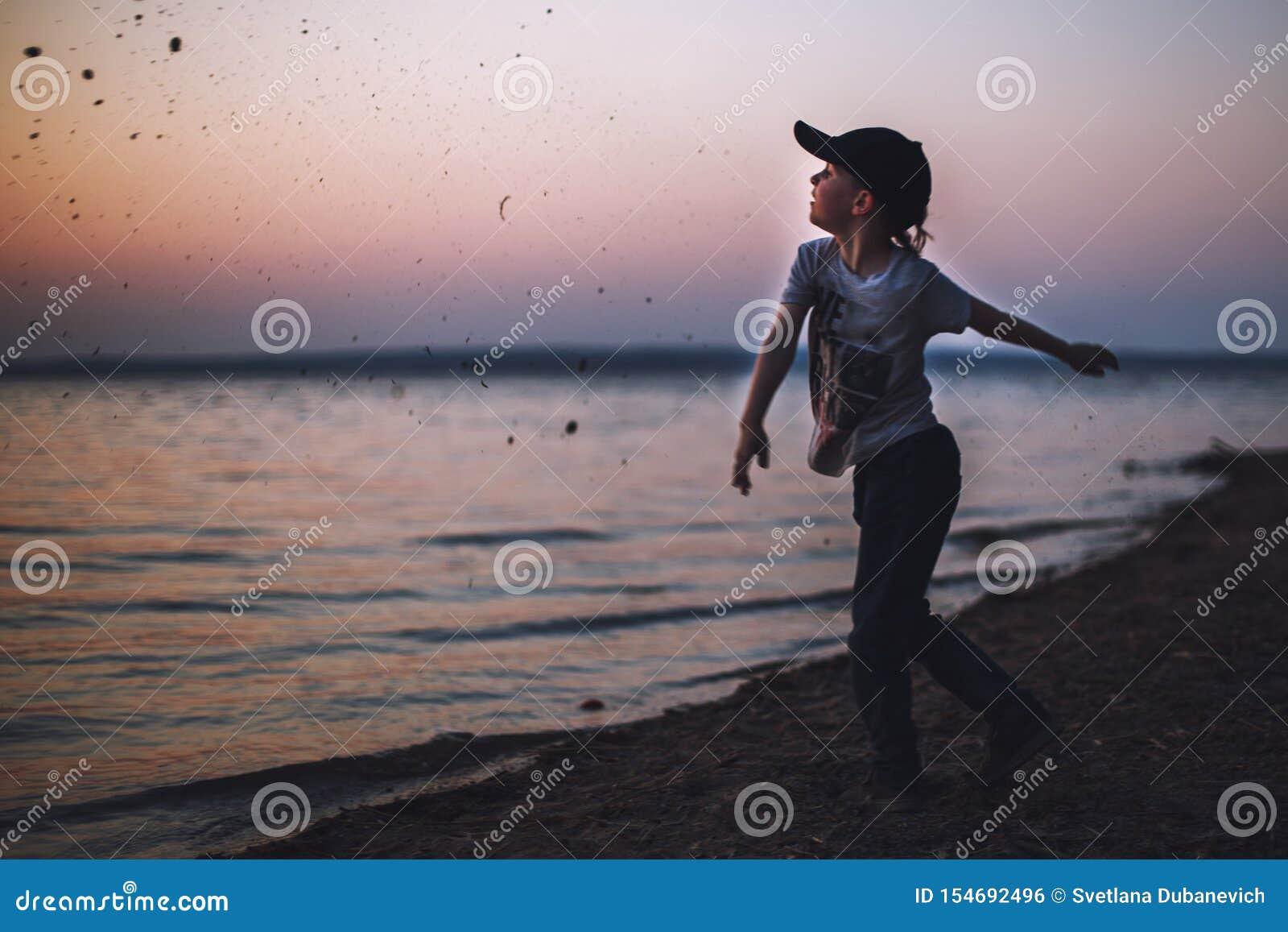 O menino na praia joga pedras na água