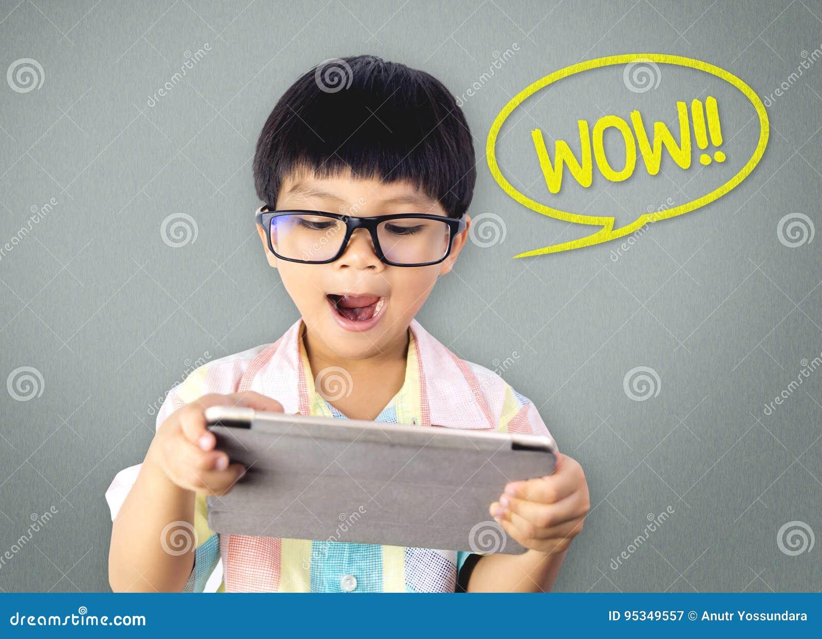 O menino nerdy asiático é emocionante com a tabuleta