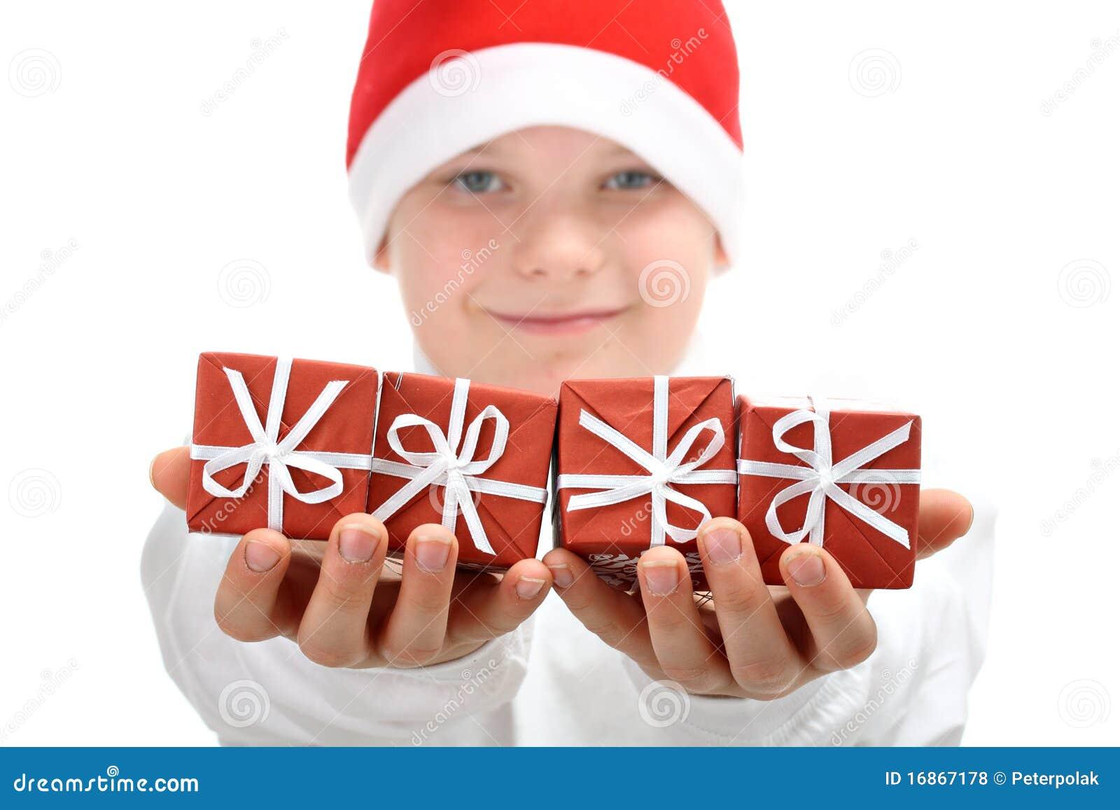 O menino no chapéu de Santa mantem presentes de Natal isolados
