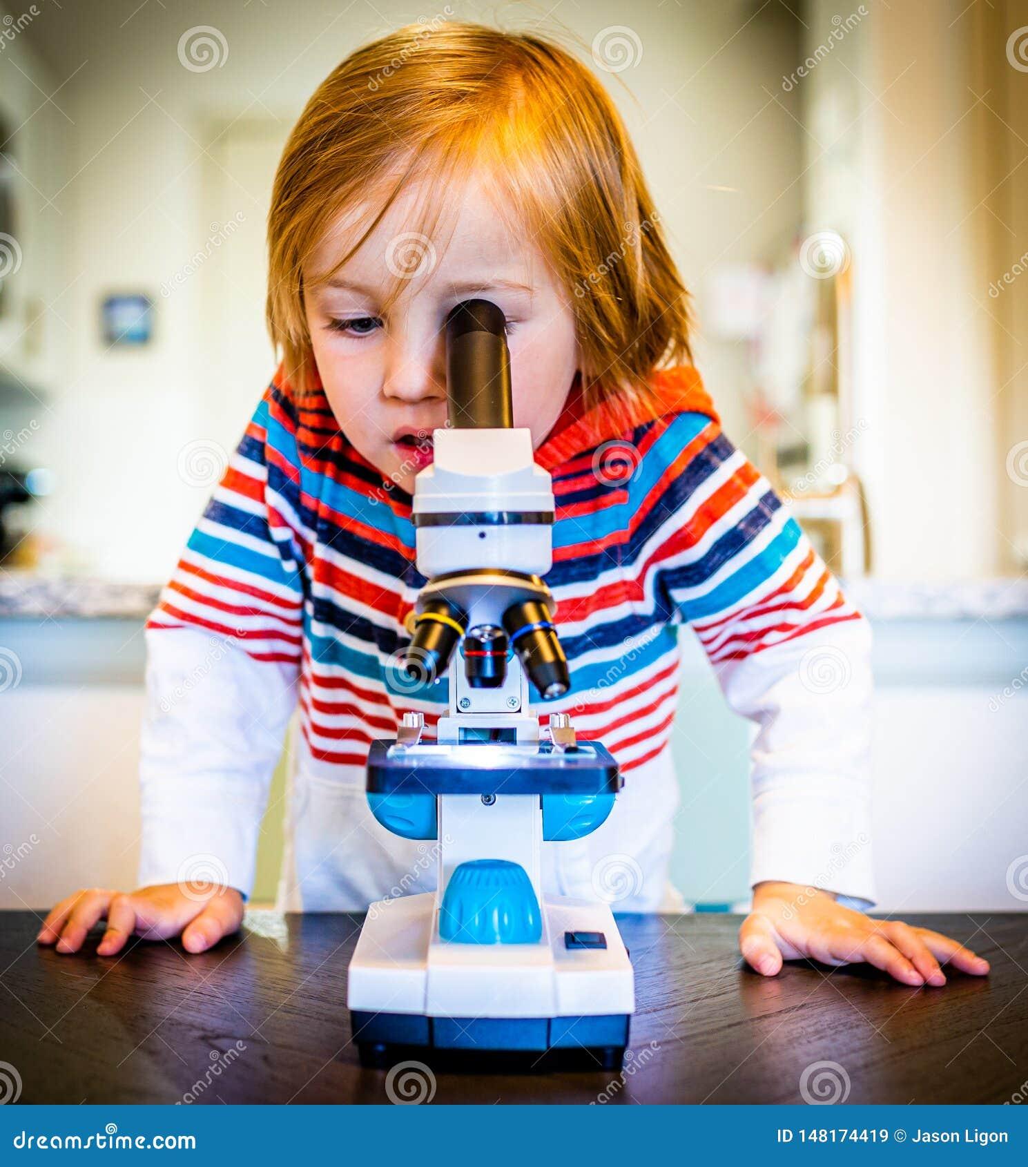O menino novo olha através do microscópio