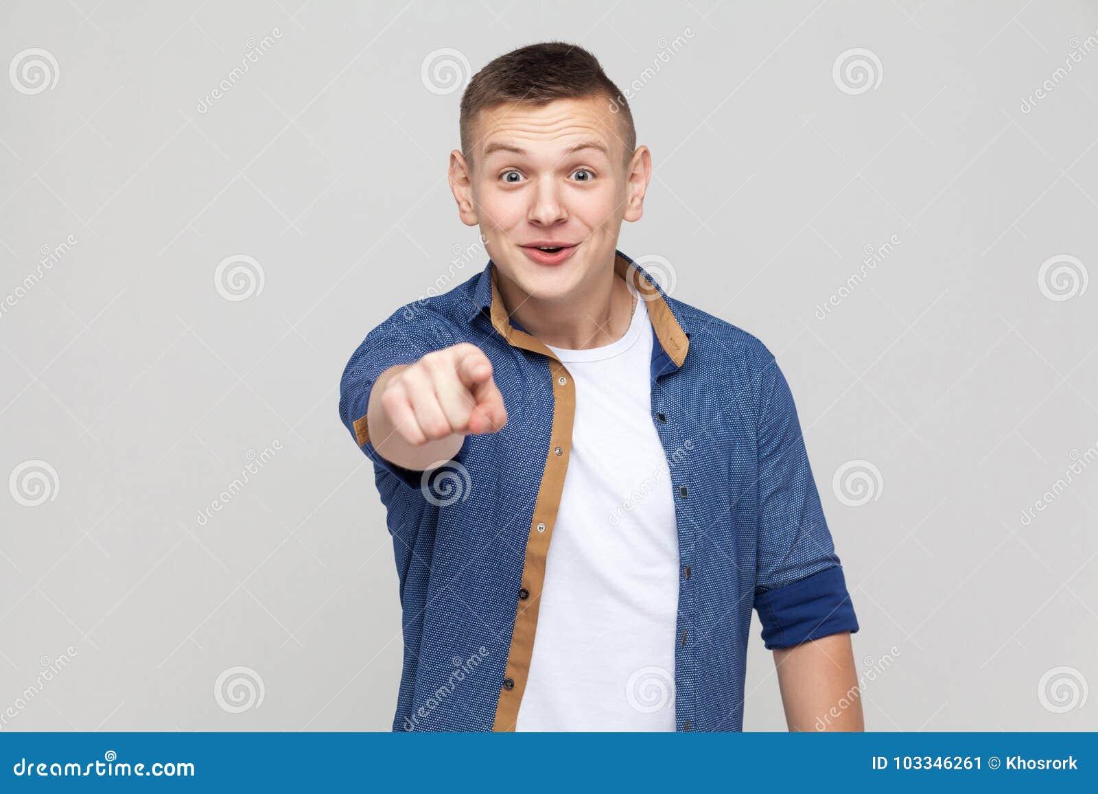 O menino que aponta o dedo na câmera e tem um olhar surpreendido