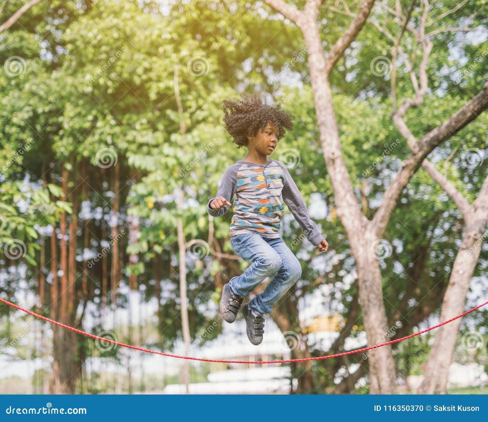 O menino que salta sobre a corda no parque no dia de verão ensolarado