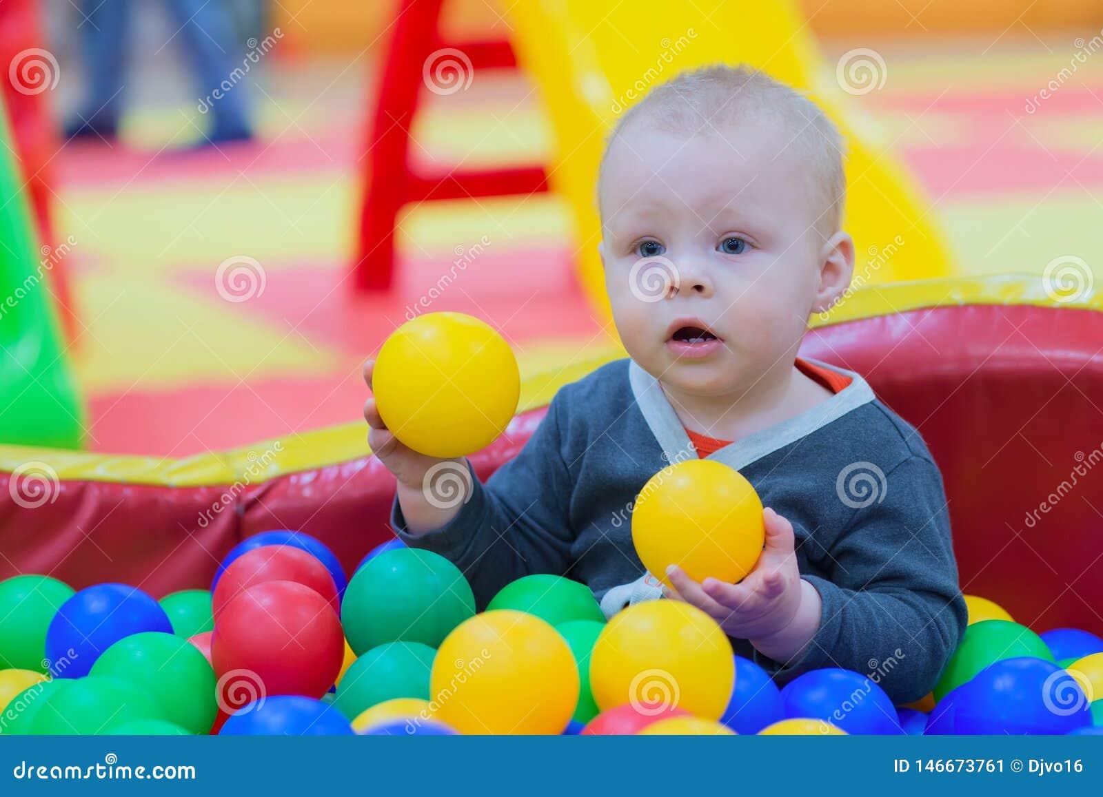 O menino senta-se em uma pilha das bolas em uma associação seca e em jogos