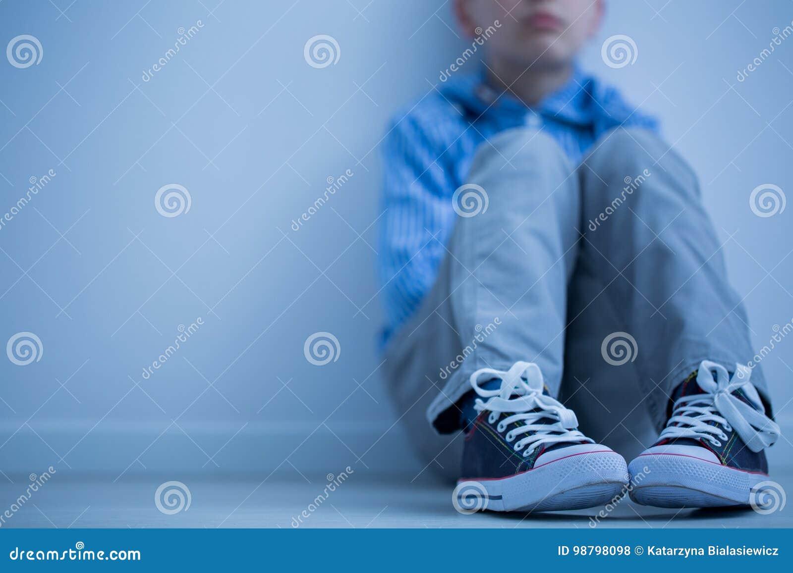 O menino triste senta-se apenas