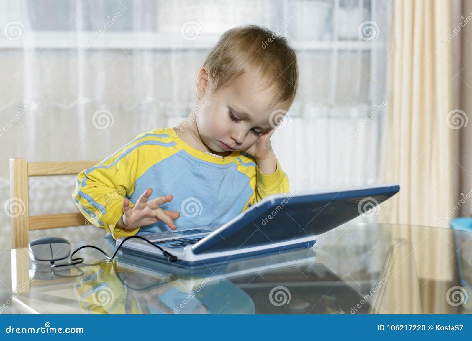 O menino usa um computador do ` s das crianças
