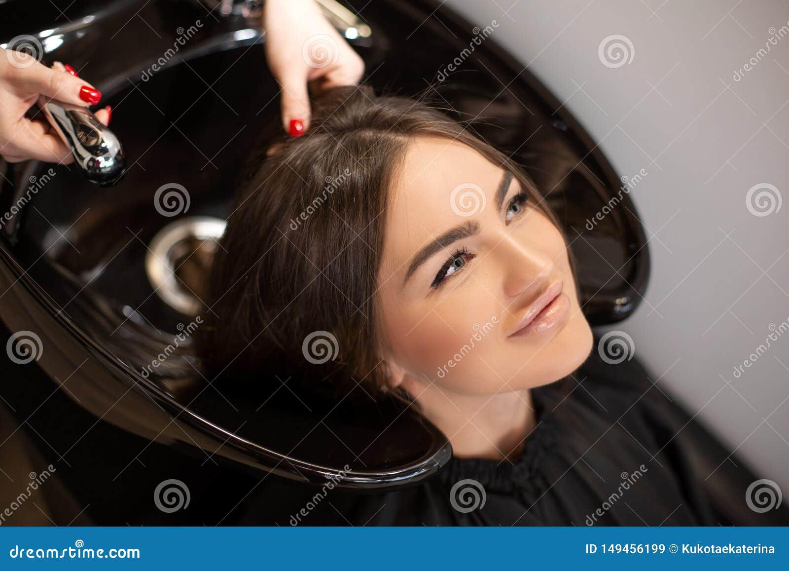 O mestre do corte de cabelo lava o cabelo de seu cliente teve