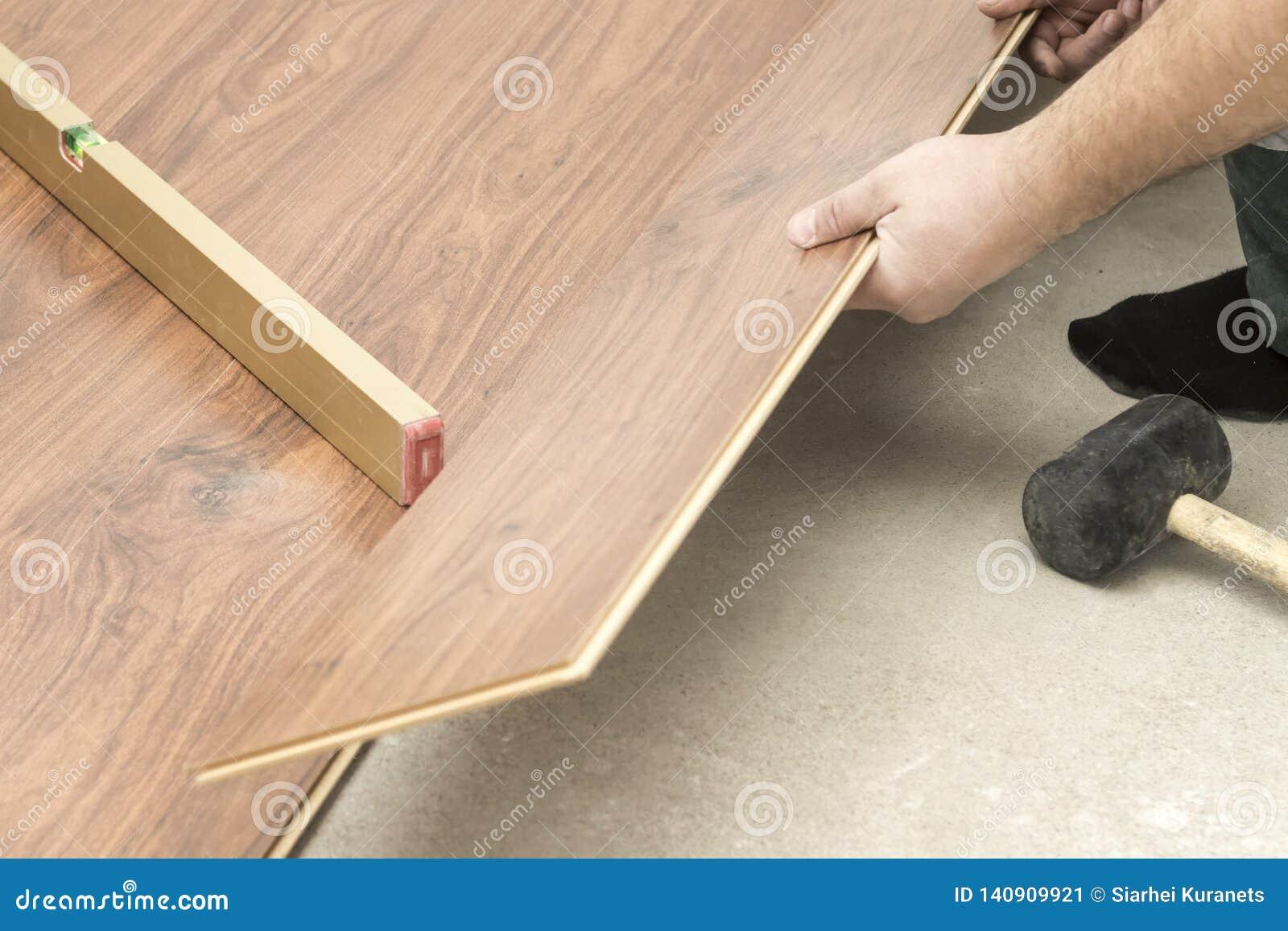 O mestre em luvas azuis faz a colocação floorboard há um nível e martelo de borracha
