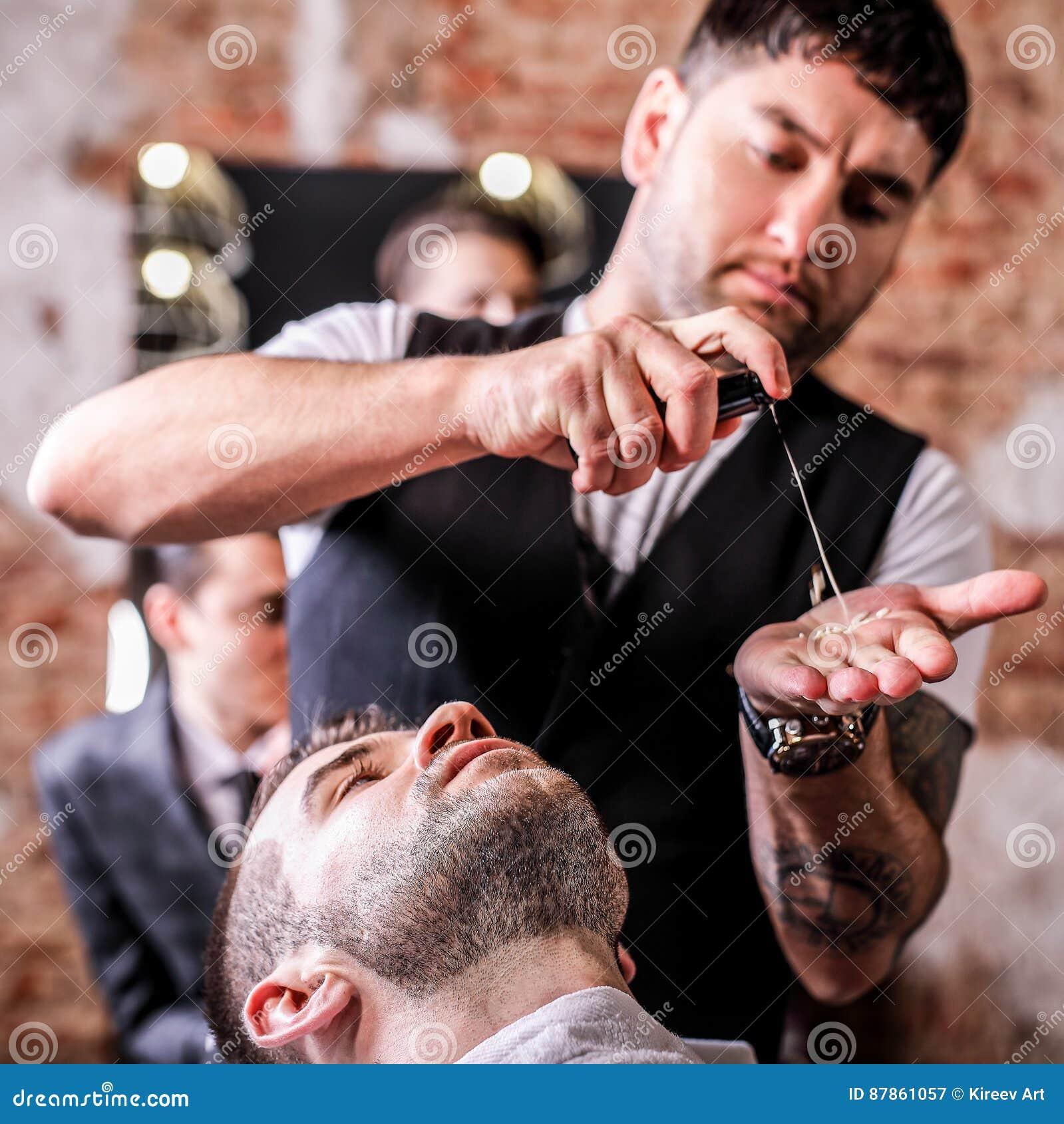 O mestre faz a correção das barbas no salão de beleza do barbeiro Feche acima da foto
