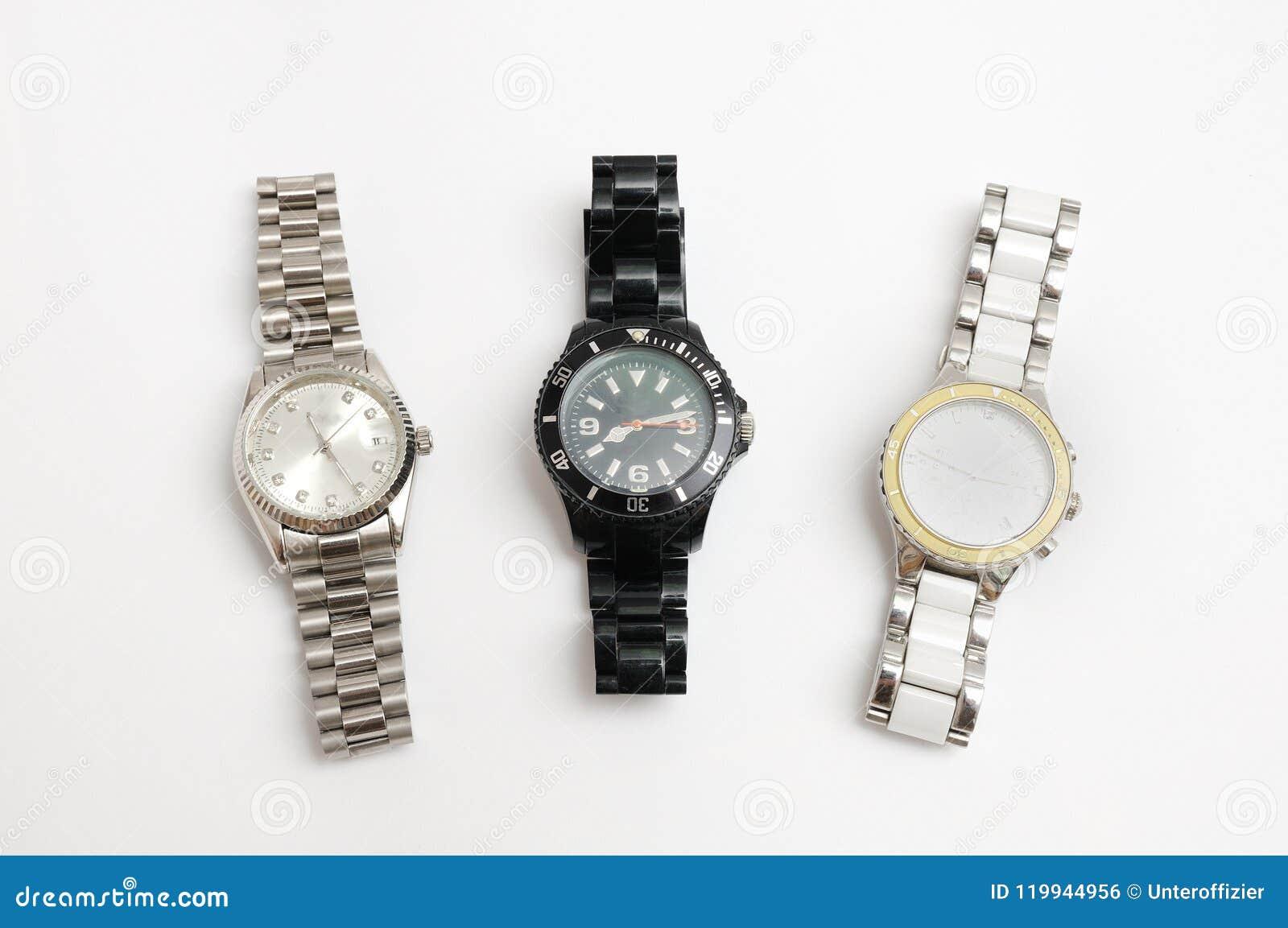 O metal três prendeu com correias relógios da cor da prata, a branca e a preta