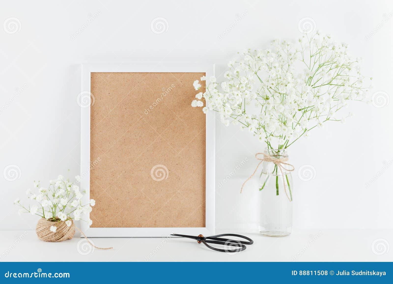 O modelo do gypsophila decorado moldura para retrato floresce no vaso na mesa de trabalho branca com espaço limpo para o texto e