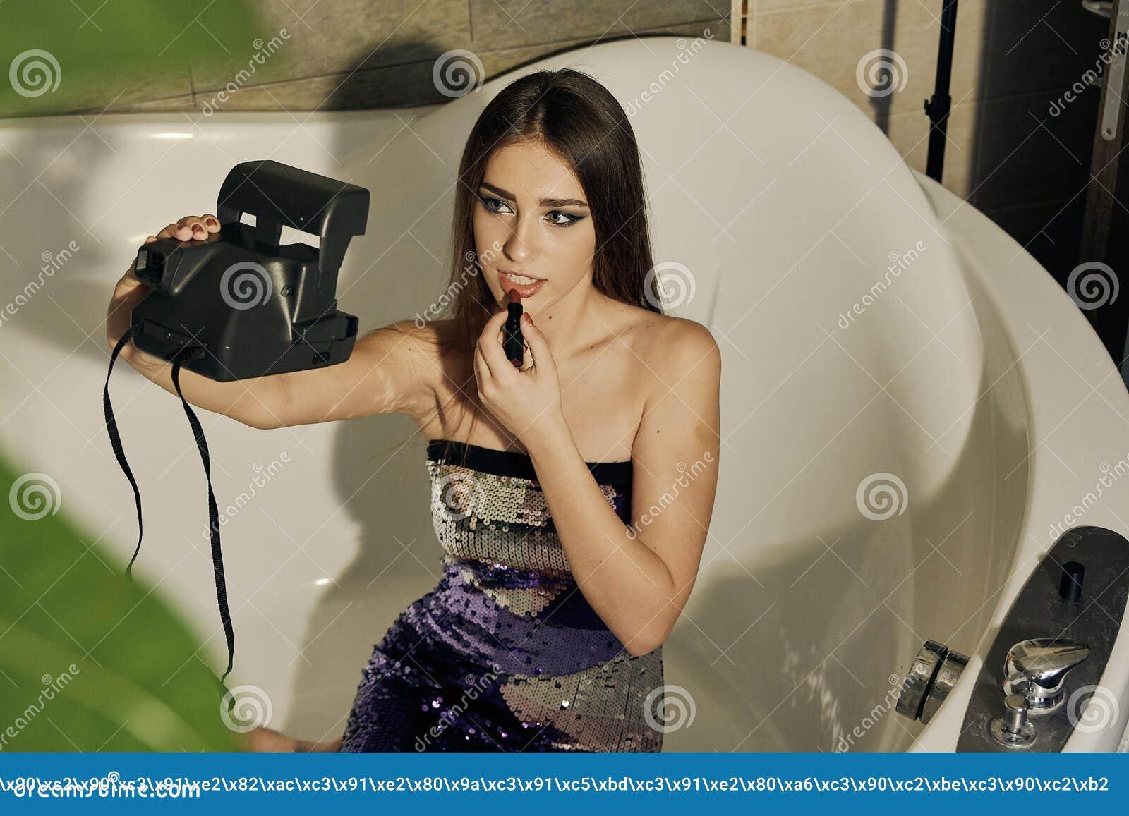 O modelo fêmea novo com o cabelo moreno longo que levanta no banho, pinta os bordos com batom e selfie fazer na câmera polaroid