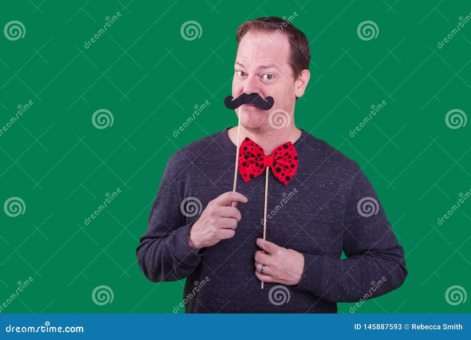 O modelo masculino que guarda o bigode falsificado para enfrentar o suporte vermelho da cabine da foto do bowtie capturou um fund