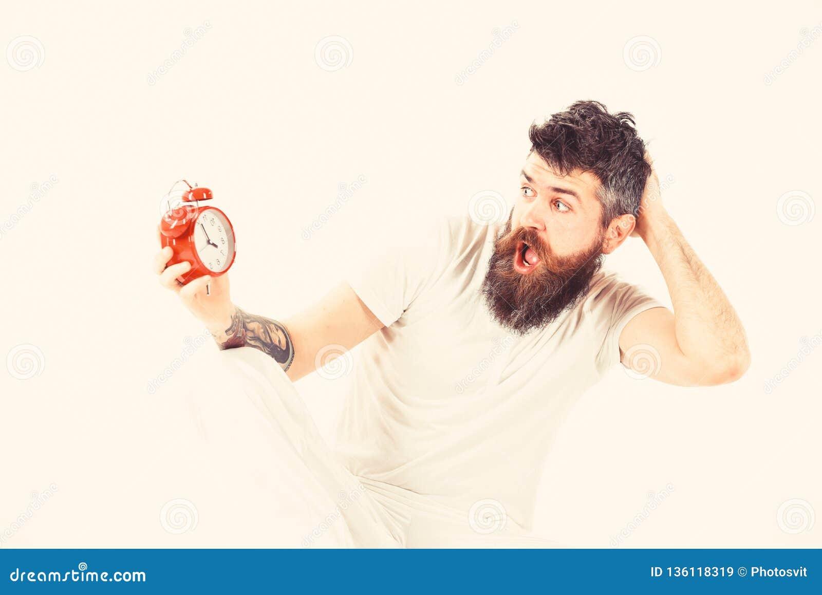 O moderno com barba e bigode durmiu demais O homem com cara chocada senta, guarda o despertador O homem precisa de levantar-se ma