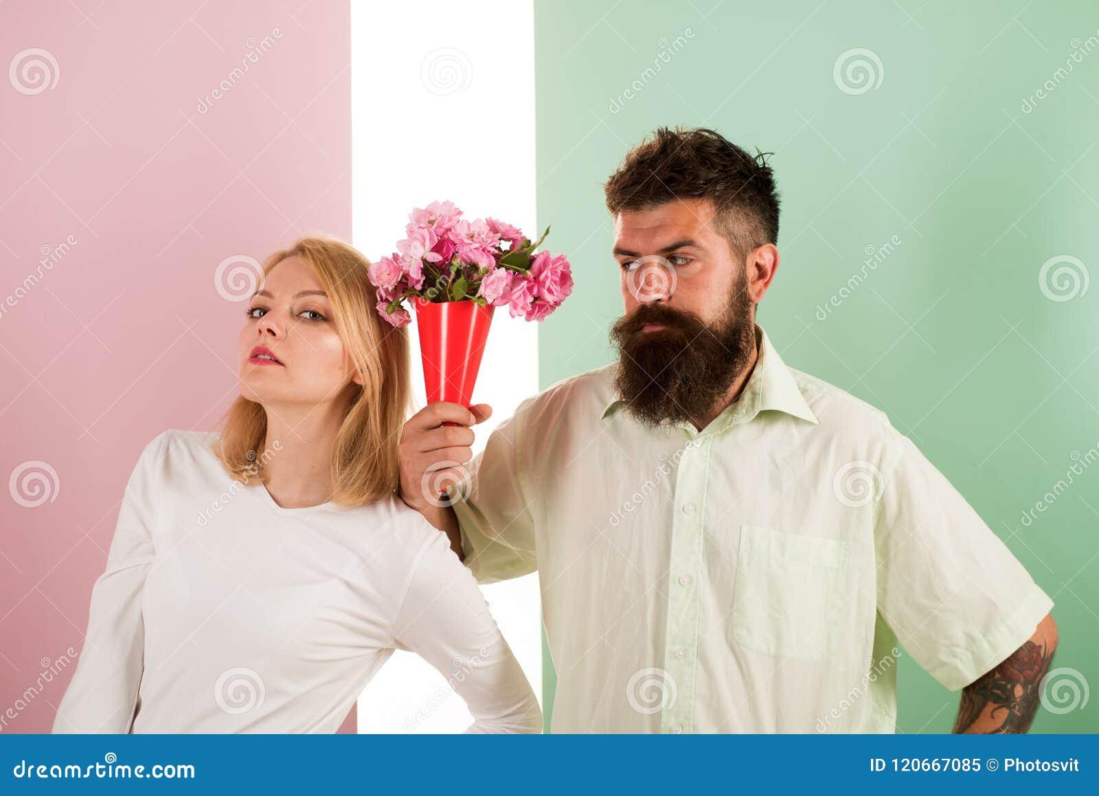 O moderno farpado dá o gesto da desculpa da menina de flores do ramalhete Homem com a mulher dos apologyes da barba Flores do ram