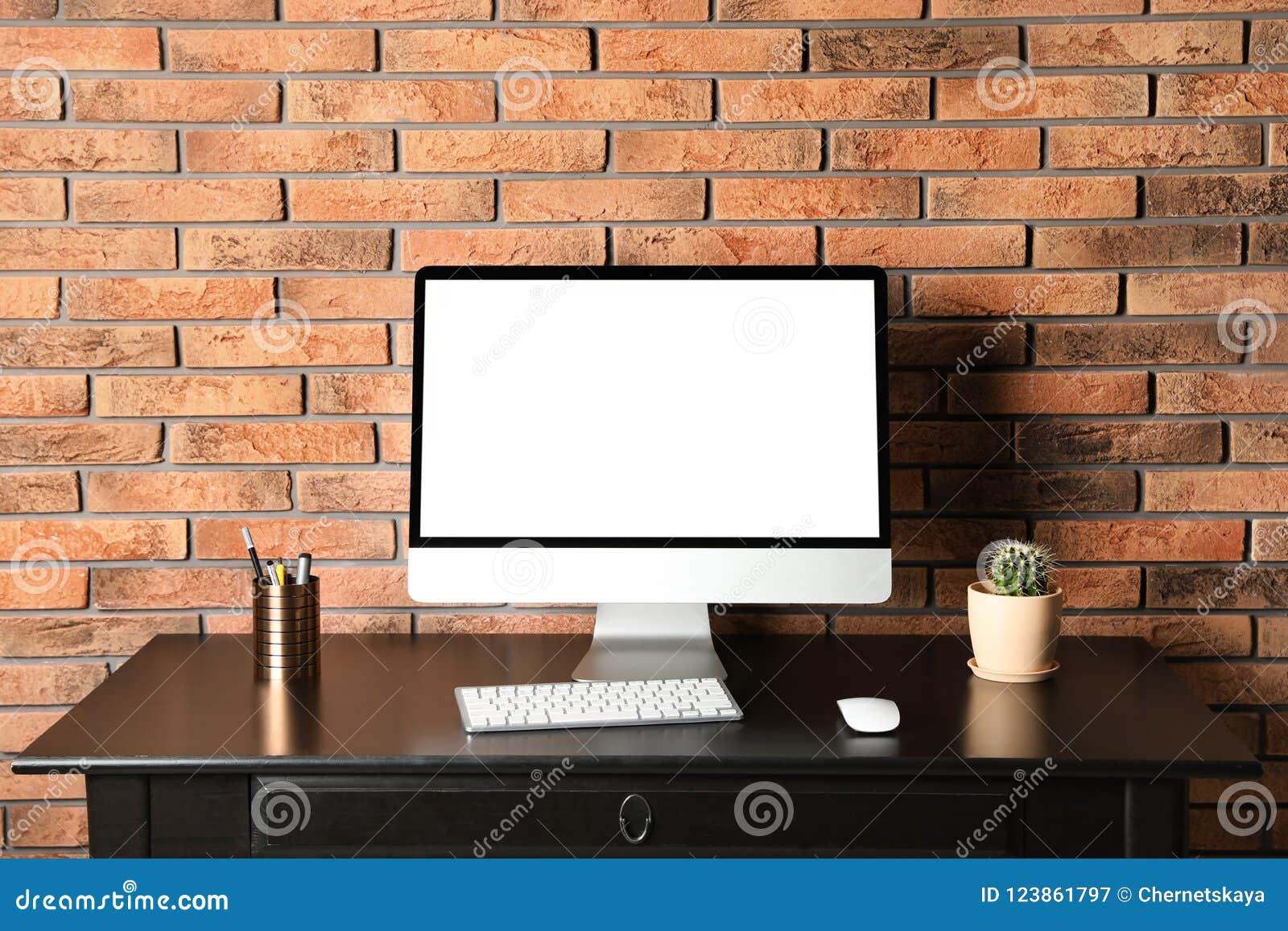 O monitor moderno do computador na parede de tijolo da mesa, zomba acima com espaço para o texto