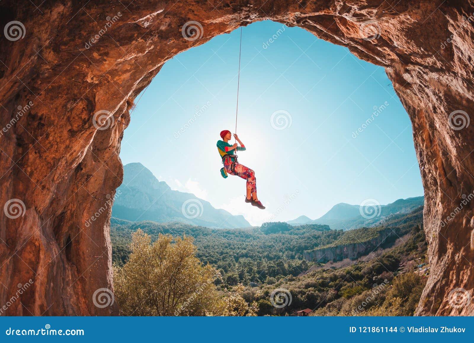 O montanhista está pendurando em uma corda