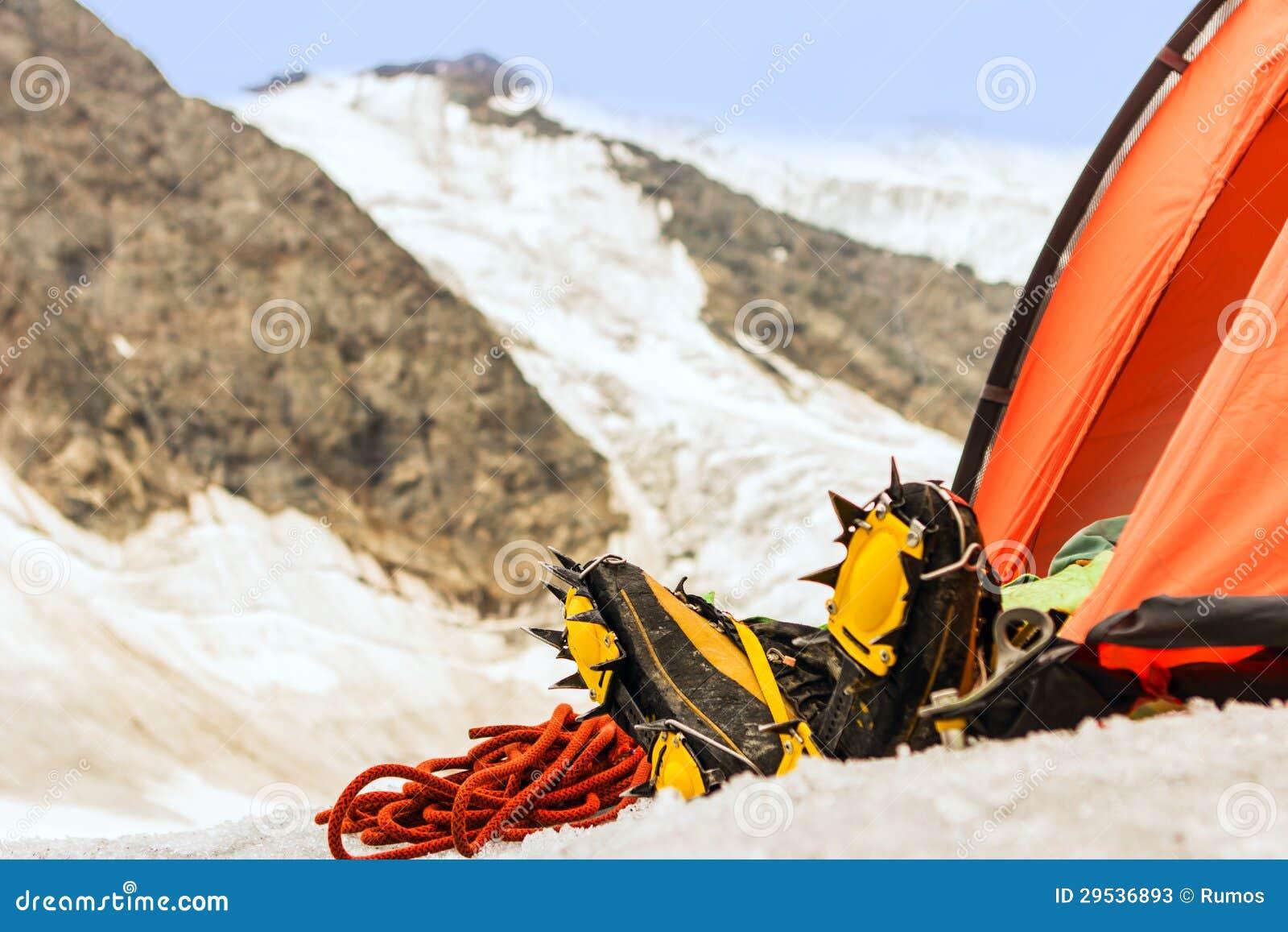 O montanhista tem o descanso na barraca altamente nas montanhas