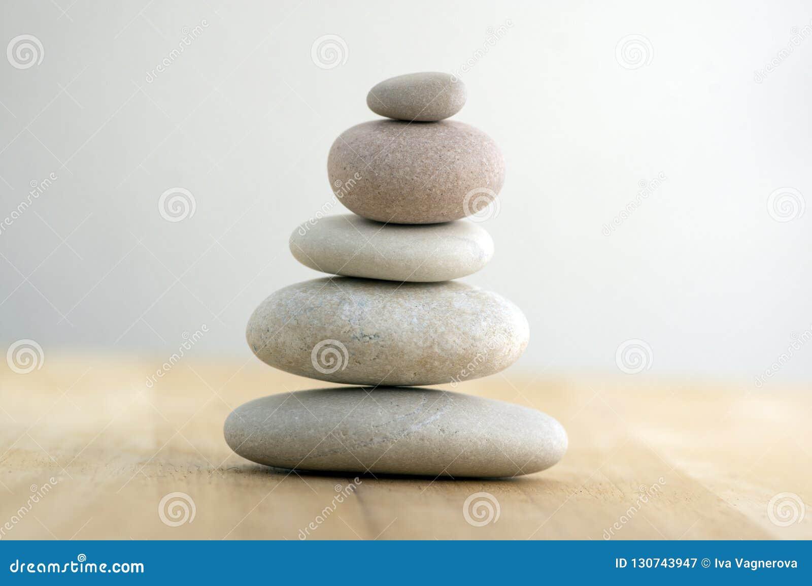 O monte de pedras de pedra em fundo branco cinzento listrado, cinco pedras eleva-se, pedras simples do porte, harmonia da simplic